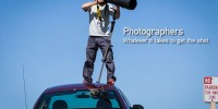 Photographer standing on a car to get the shot